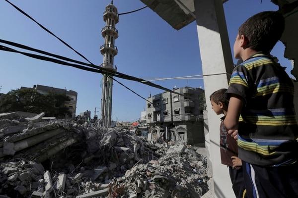Niños palestinos observan las ruinas de la mezquita de al-Kassam, alcanzada por un ataque israelí en el campo de refugiados Nusseirat, en Gaza. | AP