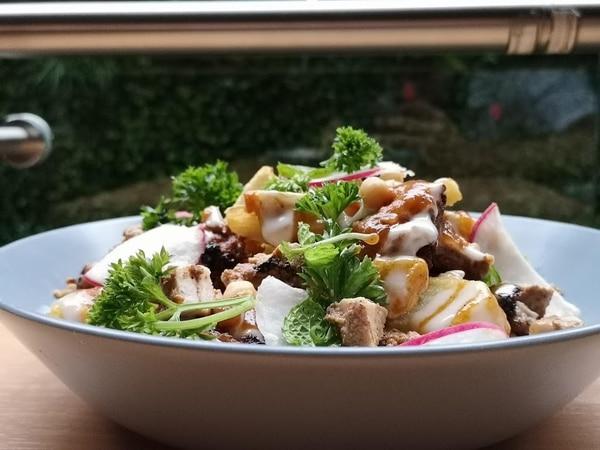 Un bowl de papas fritas cortadas a mano con toum, hummus, pollo shawarma, pepinillos, rabanitos, bbq de tamarindo, cebolla asada y hierbas. Foto: Osvaldo Calderón