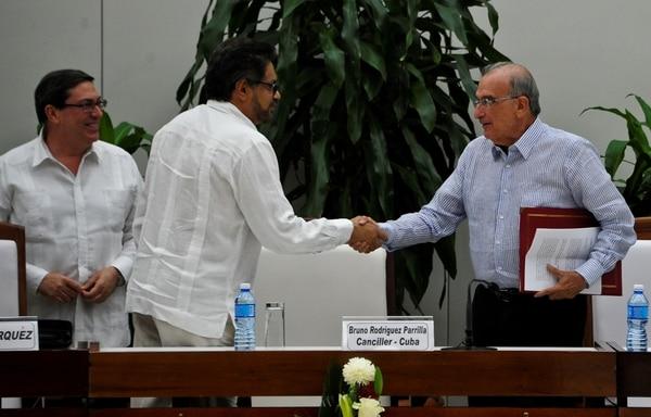 El comandante de la guerrilla de las FARC, Ivan Márquez (izq.), y el jefe de la delegación colombiana, Humberto de la Calle, se saludaron el año pasado luego de firmar el nuevo acuerdo de paz en La Habana, Cuba.