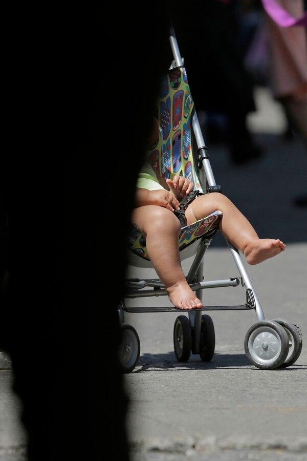 Una mujer conduce a su hijo en coche a lo largo del bulevar de la Avenida Central.