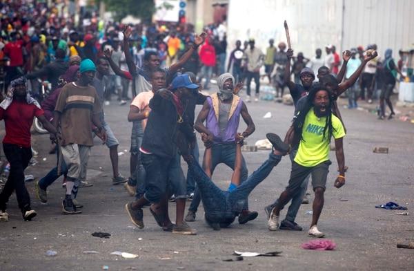 Manifestantes auxiliaban a un compañero herido durante una protesta antigubernamental en Puerto Príncipe, el martes 12 de febrero del 2019.