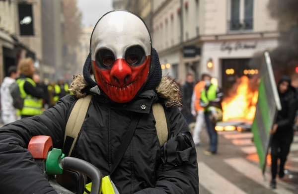 Los manifestantes de chalecos amarillos se reúnen mientras se queman materiales durante una protesta contra el aumento del precio del petróleo. Foto: AFP