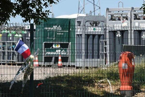 Una bandera francesa y un ramo de flores estaban ayer en las afueras de la fábrica de gas Air Products, donde ocurrió la decapitación. | AFP