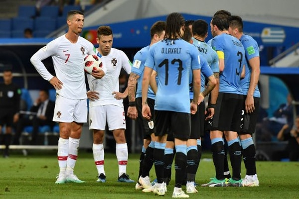 Hora de jugar. Cristiano Ronaldo espera con el balón a que los uruguayos terminen de celebrar la primera anotación del encuentro. Los europeos nunca pudieron ponerse por delante en el marcador a lo largo de los 90 minutos. / AFP PHOTO / Nelson Almeida /