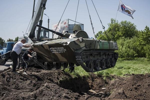 Activistas prorrusos se disponen a enterrar un tanque en un puesto de control cerca de la ciudad de Slaviansk, Ucrania. La ONU denunció la anarquía creciente en el este de ese país, en una atmósfera de persecución contra todos lo que, por su labor, puedan parecer favorables a su unidad. | EFE