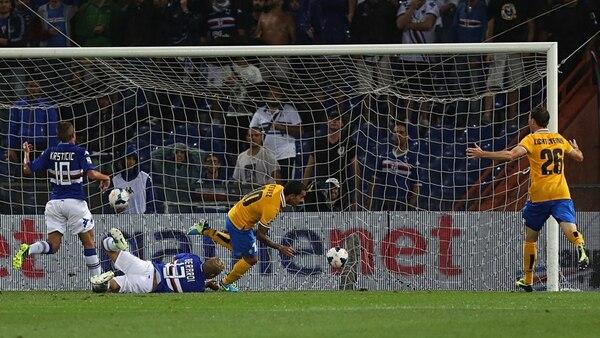 El delantero argentino Carlos Tevez (derecha), le ganó la partida al defensor Gaetano Berardi (en el suelo), para marcar el gol de la Juve. | AP