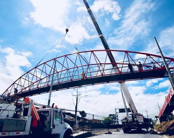 Una grúa de 400 toneladas permitió levantar la pasarela del puente peatonal en INVU Las Cañas, para colocarla sobre los anclajes que ya estaban listos. Foto: Municipalidad de Alajuela