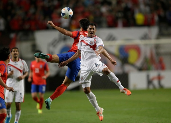 Michael Umaña le pelea el balón al coreano Lee Dong-gook.   AP