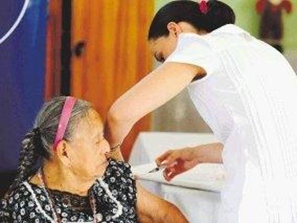 Socorro Pérez, del asilo de ancianos de Brasil de Mora, fue vacunada ayer contra la influencia por Jéssica Angulo, del equipo de la Caja. | JORGE CASTILLO.
