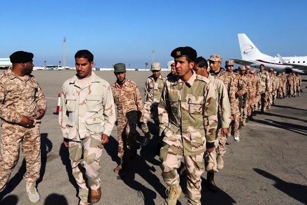 Exrebeldes quienes se unieron al Ejército de Libia se aprestan a abordar un avión en Trípoli para viajar a Italia, donde recibirán entrenamiento. | AFP