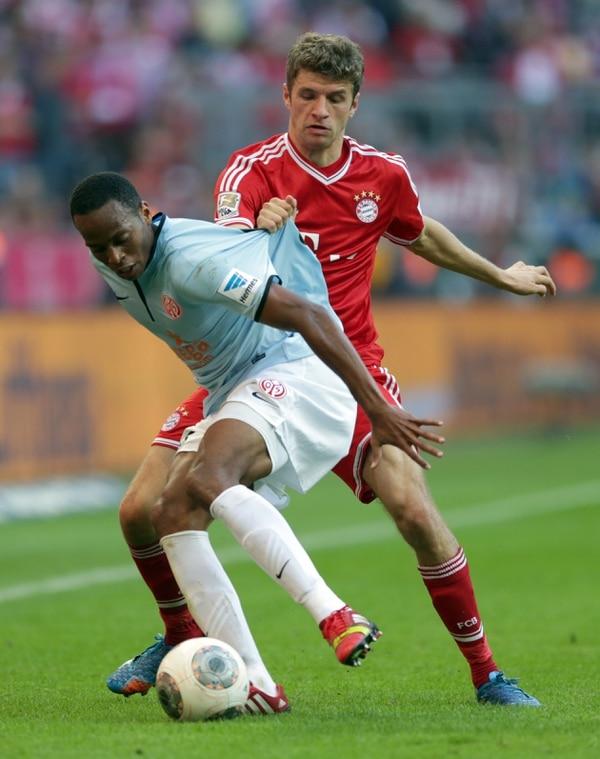 El defensor costarricense Junior Díaz protege el balón ante la marca de Thomas Mulller este domingo.