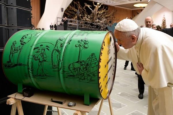 El papa Francisco observa un pasito construido dentro de este barril que le regalaron durante una audiencia, el miércoels, en el salón Pablo VI en Ciudad del Vaticano.