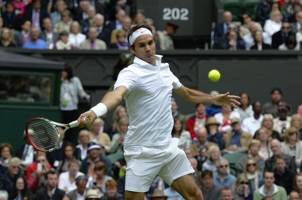Roger Federer devuelve esta pelota ante Victor Hanescu, a quien venció hoy lunes en Wimbledon, 6-3, 6-2 y 6-0.
