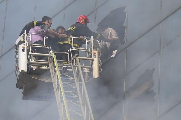 Una persona recibía la ayuda de los bomberos quienes acudieron a combatir el incendio e un edificio de oficinas en Daca, Bangladés, este jueves 28 de marzo del 2019.