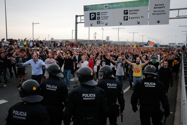 Protesters clash with Spanish policemen on the highway leading to El Prat airport in Barcelona on October 14, 2019 as thousands of angry protesters took to the streets after Spain's Supreme Court sentenced nine Catalan separatist leaders to between nine and 13 years in jail for sedition over the failed 2017 independence bid. - As the news broke, demonstrators turned out en masse, blocking streets in Barcelona and elsewhere as police braced for what activists said would be a mass response of civil disobedience. (Photo by Pau Barrena / AFP)
