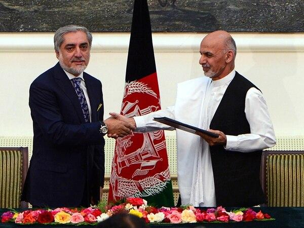 Los dos candidatos presidenciales afganos Abdulá Abdulá (izq.) y Ashraf Ghani se dieron la mano después de firmar el acuerdo para compartir el poder. El acto se llevó a cabo ayer en el palacio presidencial en Kabul.   AFP