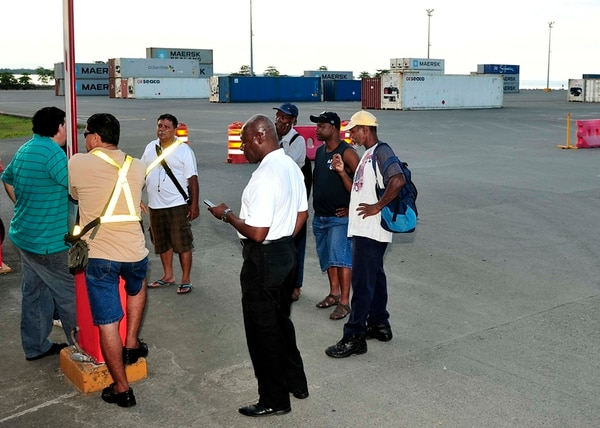 Trabajadores y miembros del sindicato de Japdeva que apoyan la huelga en las instalación del muelle, con los contenedores de fondo. | JOHN DURÁN