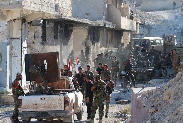 Tropas sirias se desplazaban el sábado entre los escombros en el campo de refugiados palestinos de Handarat, al norte de Alepo, adonde entraron luego de bombardeos aéreos rusos.
