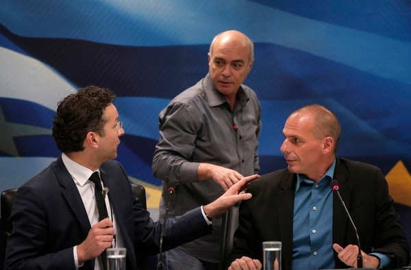 El ministro griego de Finanzas, Yanis Varoufakis (derecha), observa mientras el presidente del Eurogrupo, Jeroen Dijsselbloem (izquierda), conversa con un técnico en relación con un problema en el equipo de traducción durante la rueda de prensa ayer en Atenas. | AP