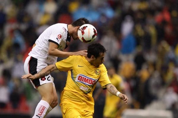 Elías Palma disputa el balón con el jugador del América Rubens Sambueza.
