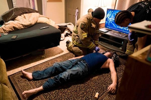 Los bomberos de Machester atienden a un hombre con sobredosis de heroína. AFP PHOTO / Don EMMERT