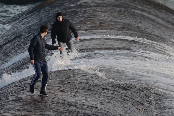 La gente ve el oleaje desde el malecón del puerto de Les Sables-d'Olonne, al oeste de Francia, durante la marea inusualmente alta de este sábado 21 de marzo.