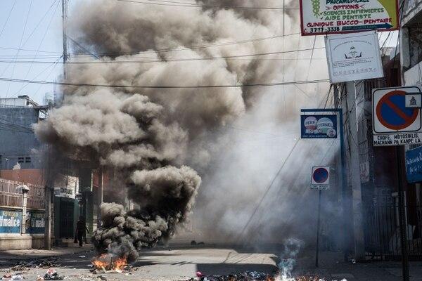 Escombros ardían en medio de protestas contra el gobierno del presidente Jovenal Moïse, el miércoles 30 de octubre del 2019 en Puerto Príncipe.