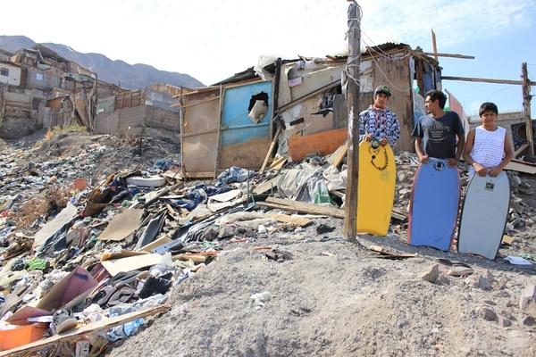 Arturo Soto (centro), joven emprendedor chileno, dirige una escuela de surf para niños en riesgo social. | EFE