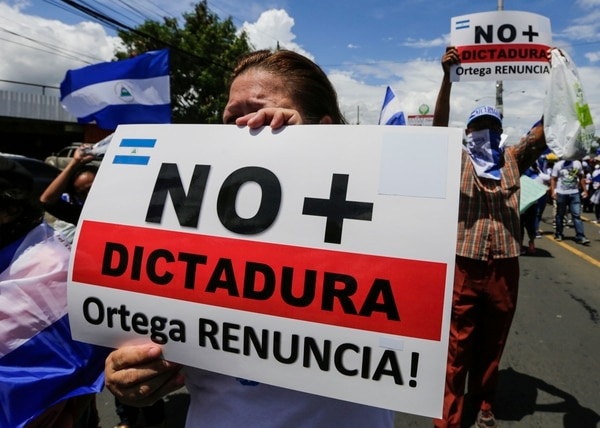 Una manifestante antigubernamental sostiene una pancarta que dice 'No más dictadura', mientras participa este miércoles en una marcha para exigir la liberación de presos políticos en Managua. Foto: AFP
