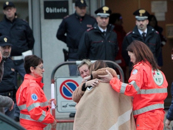 Familiares y amigos se consuelan mutuamente fuera de la morgue en Corinaldo, Italia.