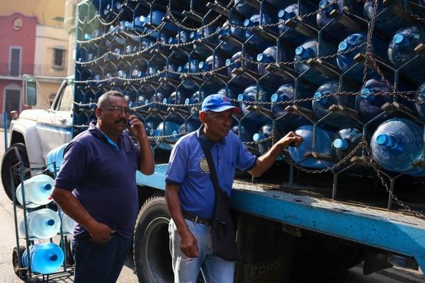 Trabajadores distribuían bidones de agua, este miércoles 27 de marzo del 2019, en Caracas, que sigue sin energía eléctrica.
