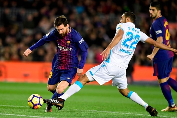 Barcelona's Argentinian forward Lionel Messi (L) vies with Deportivo La Coruna's Costa Rican forward Celso Borges during the Spanish league football match FC Barcelona against RC Deportivo de la Coruna at the Camp Nou stadium in Barcelona on December 17, 2017. / AFP PHOTO / JAVIER SORIANO