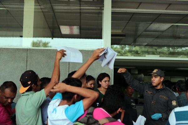 Un oficial de migración costarricense solicita documentos a nicaragüenses que solicitan refugio en Peñas Blancas. Foto Alonso Tenorio