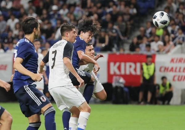 El mediocampista japonés Takumi Minaminocabecea el balón ante la mirada del lateral izquierdo tico Luis Hernández. Foto: AFP