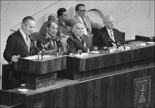 Shimon Peres(izquierda) habló ante la Kneset (Parlamento) en Jerusalén. Lo escuchaban el presidente Anwar al-Sadat (centro) y el canciller israelí, Isaac Shamir (penúltimo a la derecha). Fue con motivo de la histórica visita de Sadat a Israel en noviembre de 1977.