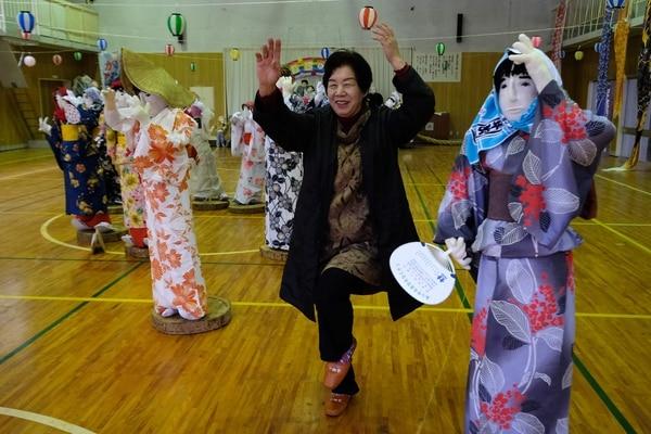 Tsukimi Ayano, habitante de Nagoro, posa con varias muñecas de tamaño real en una escuela primaria, que se cerró hace siete años, ya que no había nadie para enseñar. (Kazuhiro NOGI / AFP)
