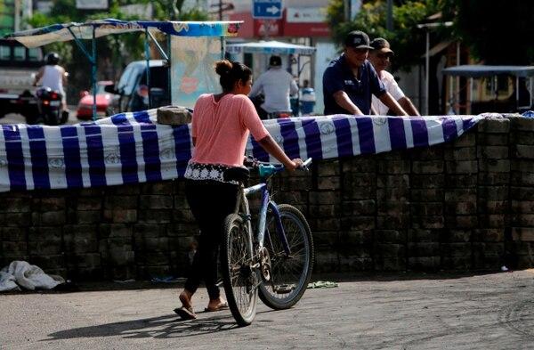 Una mujer pasa frente a una barricada en la localidad de Sebaco, a 100 kilómetros de Managua, este 13 de junio. Una gran cantidad de retenes frenan el tránsito por Nicaragua, pese a que este miércoles hubo unos pequeños avances en algunos sectores. Foto: AFP /Inti Ocón