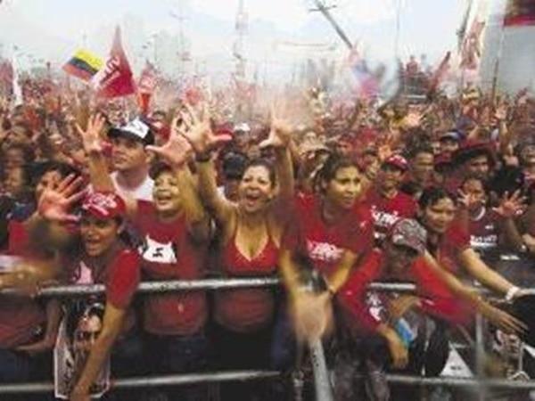 Simpatizantes de Hugo Chávez lo vitorearon ayer en el mitin de cierre de campaña electoral en una avenida en el corazón de Caracas. | AFP