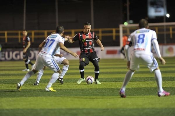 Juan Gabriel Guzmán maneja el balón ante la marca de los jugadores de la UCR.