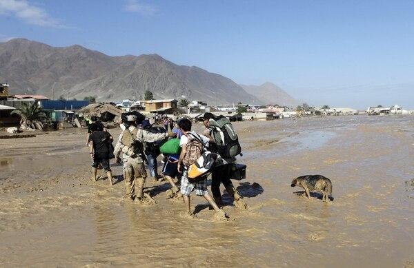 Un soldado chileno ayuda a un grupo de personas afectadas a cruzar el caudal del río formado tras las inundaciones torrenciales de hace dos días.