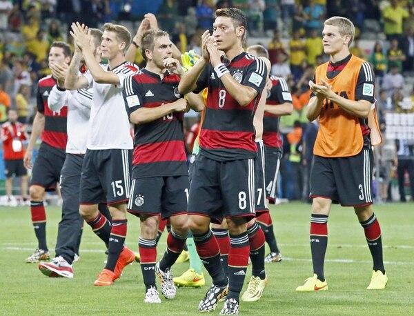 El alemán Mesut Özil (8, izq.) y el argentino Marcos Rojo (16, der.) celebran con sus compañeros el pase a la final de Brasil 2014. | EFE