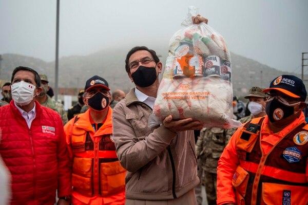 El presidente peruano, Martín Vizcarra, cargó una bolsa con productos básicos para distribuir entre afectados por la covid-19 en Villa María del Triunfo, al sur de Lima. AFP