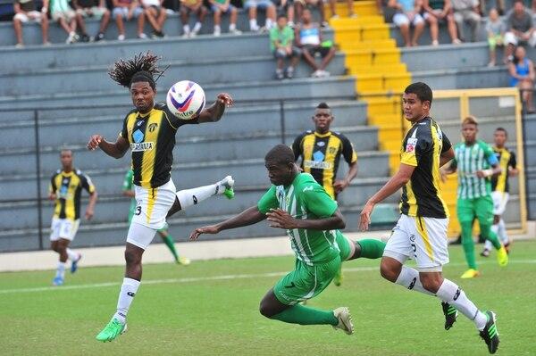 El delantero limonense Mayron George (7), disputa el balón con el defensor uruguayo Roy Smith (izquierda) en el juego de este domingo en el estadio Juan Gobán de Limón.