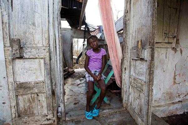 Love Manie Simeus, de 12 años, junto a lo que quedó de la casa de su abuela en la aldea de Mersan, en Les Cayes, Haití. Como miles más, el huracán la dejó en el desamparo.