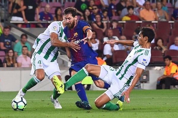 Lionel Messi conduce el balón, ante la presión del Betis.