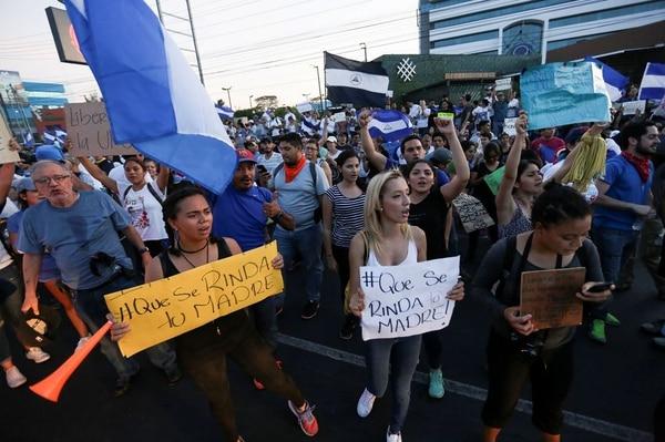 Los manifestantes sostienen carteles que dicen