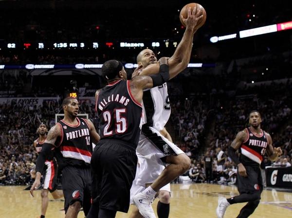Tony Parker (9), de los San Antonio Spurs ante la marca de Mo Williams (25), del Portland Trail Blazers.