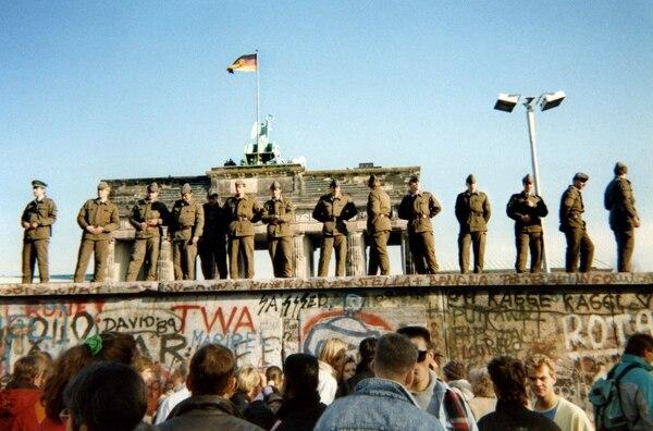 El 11 de noviembre de 1989, guardias fronterizos de Alemania Oriental se paran en una sección del muro de Berlín con la puerta de Brandenburgo al fondo en Berlín. Foto: AFP