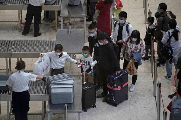 Los pasajeros cruzan el control de seguridad en la sala de embarque de la estación de trenes de alta velocidad en Hong Kong, este jueves 23 de enero del 2020. China cerró una ciudad de más de 11 millones de personas el jueves, deteniendo el transporte y advirtiendo sobre reuniones públicas, para intentar para detener la propagación de un nuevo virus mortal que ha enfermado a cientos y se ha extendido a otras ciudades y países en la carrera de viajes del Año Nuevo Lunar. Foto: AP