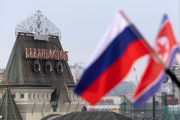 Frente a la estación central de trenes en Vladivostok colocaron banderas de Rusia y Corea del Norte, el 24 de abril de 2019. Foto: AP